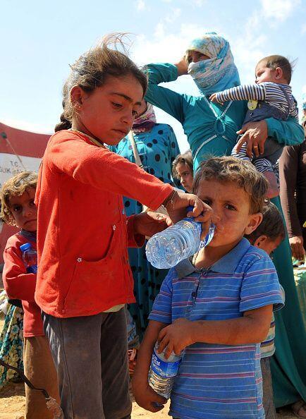 Esta niña refugiada ayuda a su hermano a beber agua después del pesado é...