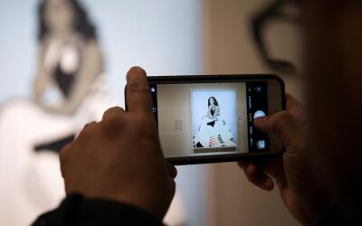Un visitante toma una foto del retrato de Michelle Obama en la National...