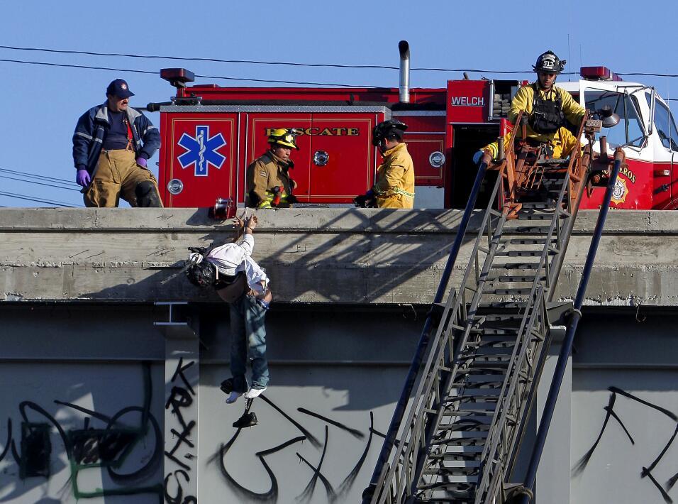 Bomberos retiran el cadáver de un hombre colgado en un puente.