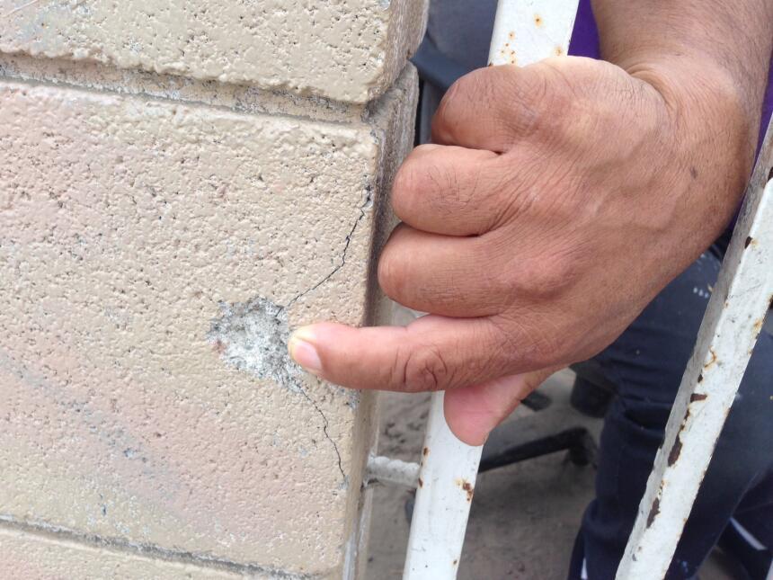 Un vecino de Compton, California, señala la perforación de una bala en l...