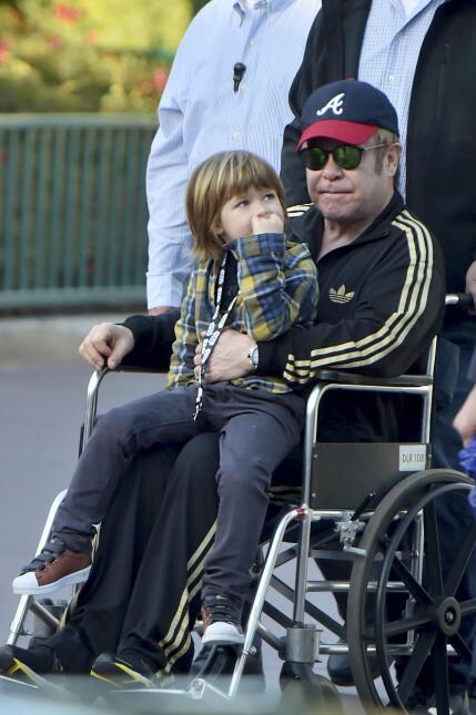 Elton John is pushed around disneyland in a wheelchair while spending a...