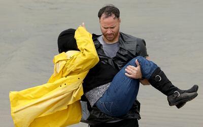 Un voluntario carga a una damnificada luego del paso del huracán...