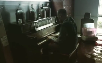 Aric Harding plays the piano inside his flooded home.