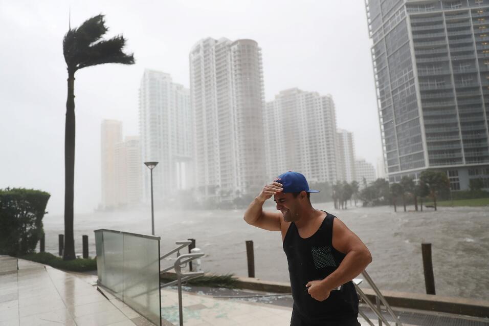 Un residente del centro de Miami lucha contra la fuerza de Irma, junto a...