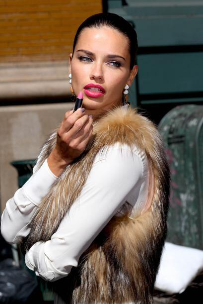 La modelo aparece pintando esa boquita con un labial fucsia.