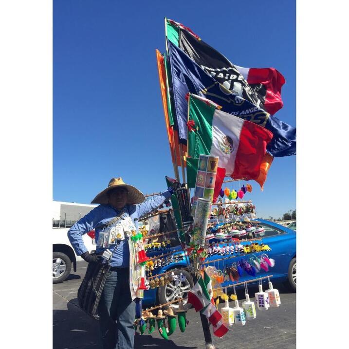 Un hombre vende banderas y decorativos para autos.