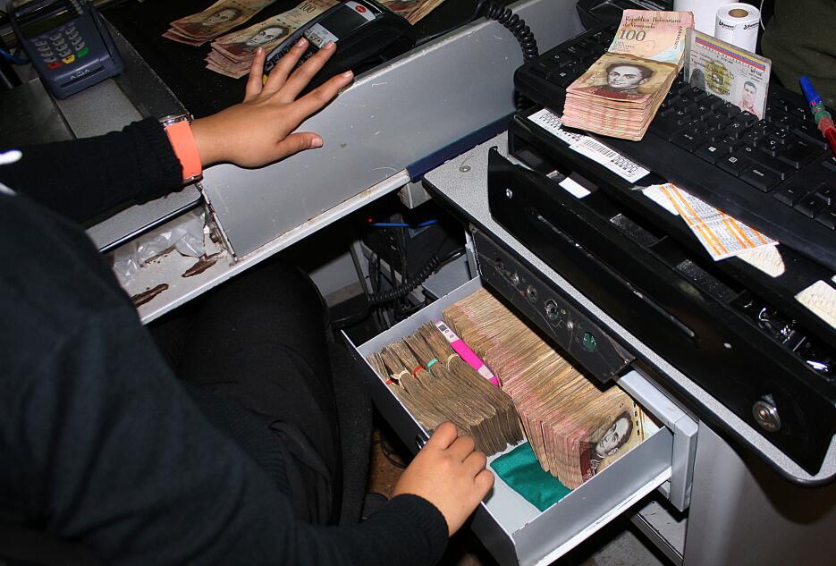 En el estado fronterizo de Táchira, una mujer almacena pacas de billetes...