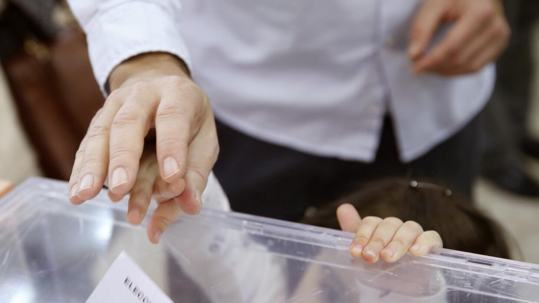 Un padre empuja el voto con el dedo de su pequeña hija en Madrid