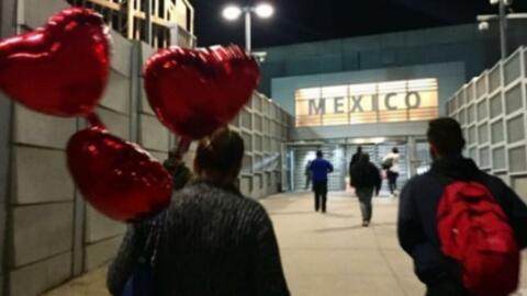 Una mujer que lleva globos de helio cruza de San Diego a Tijuana.
