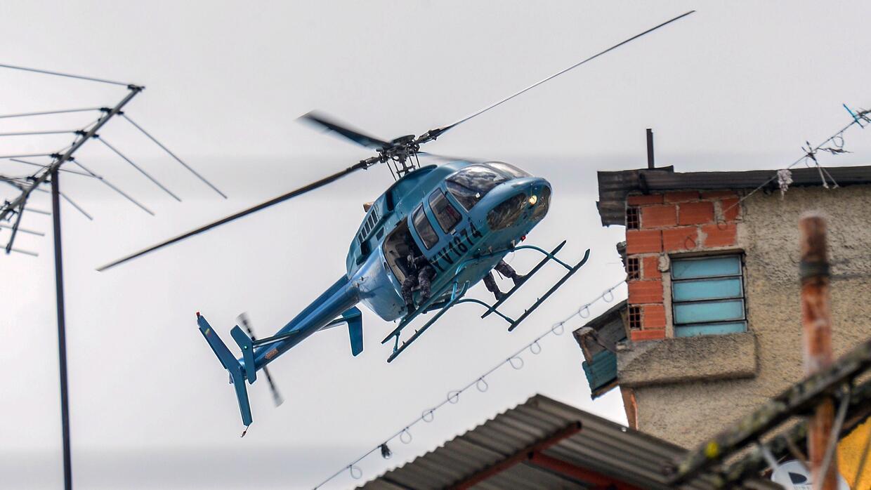 Un helicóptero de la Guardia Nacional sobrevuela un barrio de Caracas, e...