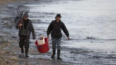 Residentes del área afectada por el derrame caminan por una de las playa...