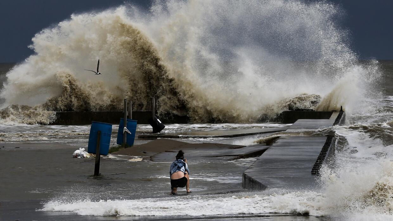 Sydney Schultz toma fotos de olas al lado del Rollover Pass mientras la...