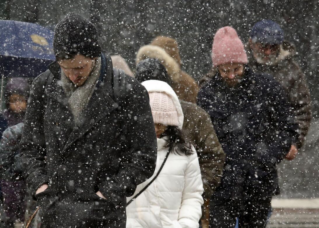 Gente caminando bajo una copiosa nevada en Brooklyn, NY