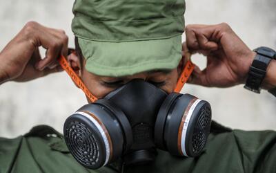 Un miembro del ejército se pone una máscara antigas antes...