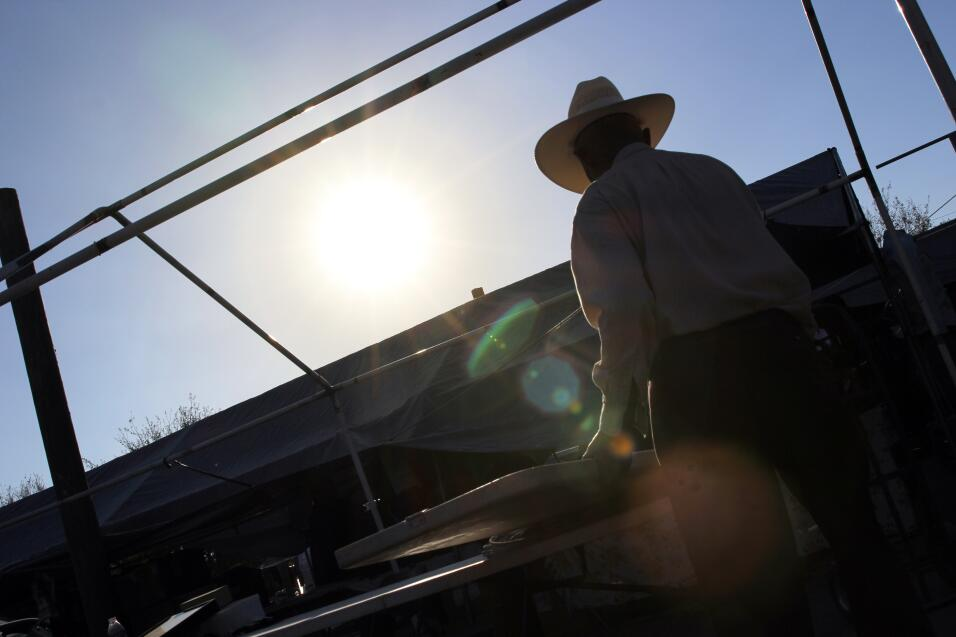 Un vendedor ambulante recoge su estante en un mercado al aire libre que...