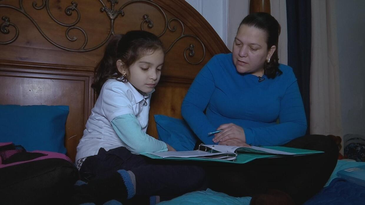 Arlette and her mother Clotilde read and practice together to prepare fo...