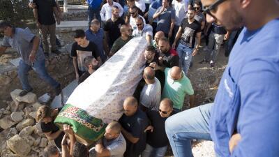 Varios hombres cargan el cadáver de Yussef Utman, uno de los guardias mu...
