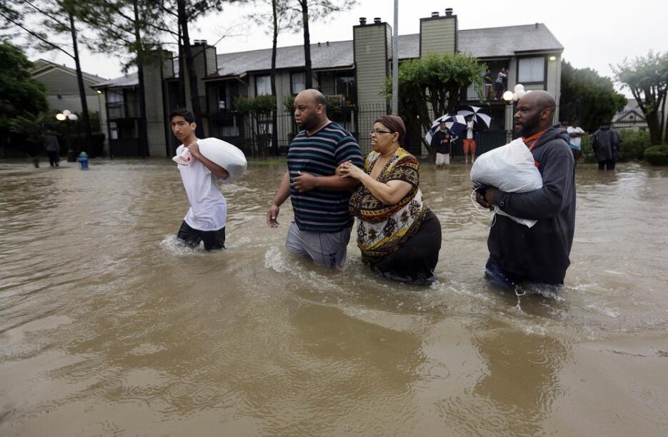 Darius Simon (segundo por la izquierda) ayuda a su madre a evacuar su ap...