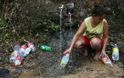 Una mujer recoge agua de manantial en Utuado, uno de los pueblos m&aacut...