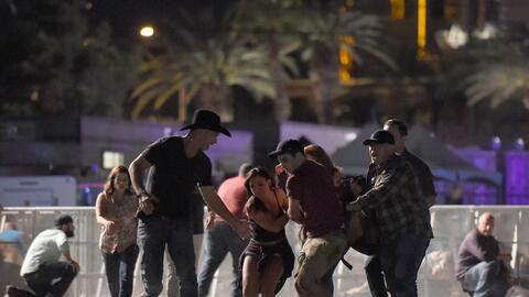 People assist a woman injured by a spray of bullets in Las Vegas.