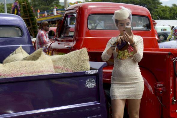Una mujer toma fotos durante un desfile de coches clásicos en el marco d...