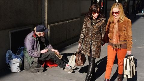 Un hombre pidiendo dinero en la opulenta avenida Madison, en Manhattan.
