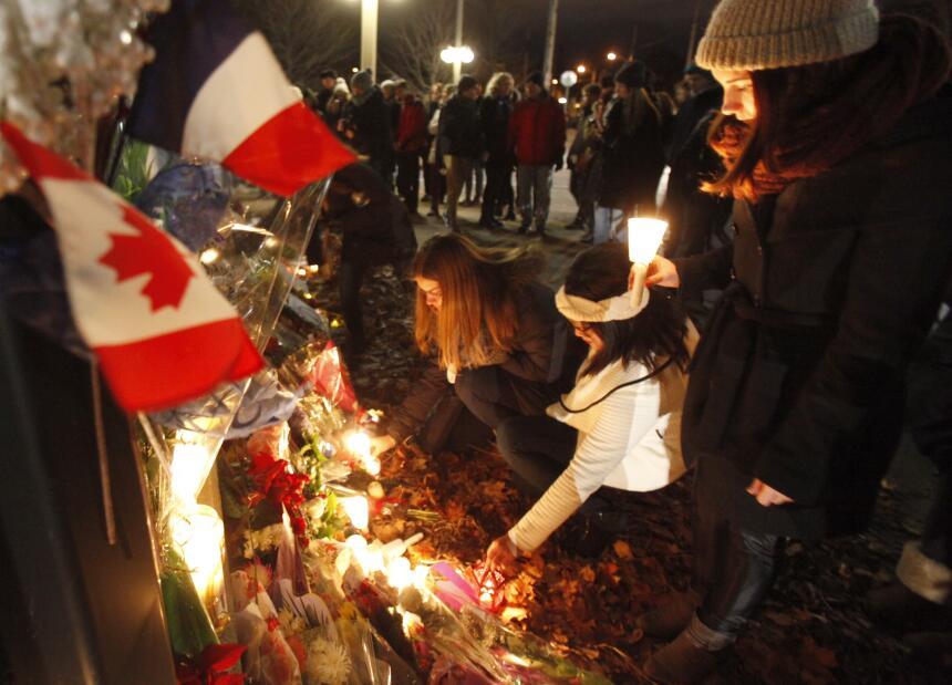 Un grupo coloca velas y flores frente a la embajada de Francia en Ottawa