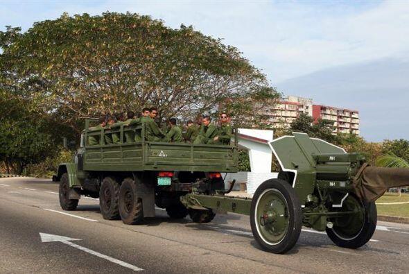Militares cubanos viajan en un camión que remolca un cañ&o...