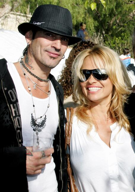 Musician Tommy Lee and actress Pamela Anderson pose at the home of John...