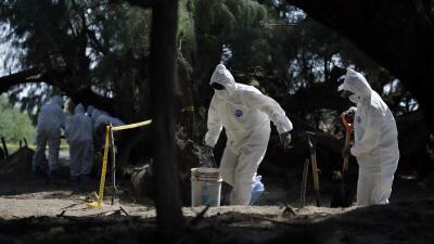 Trabajadores forenses trabajan en retirar restos humanos hallados en un...