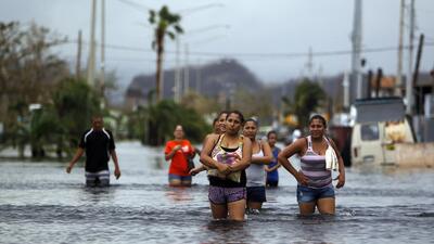 Residentes de San Juan caminan por las aguas de las calles inundadas. El...