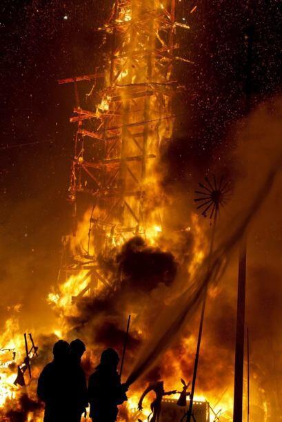 Los bomberos rocían con agua las palmeras cercanas a la Falla de...