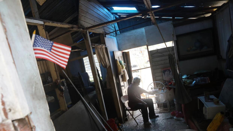 Un residente de San Isidro, en Puerto Rico, decora su casa afectada por...