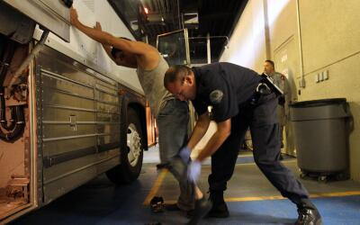 Un indocumentado es revisado por un agente migratorio en una terminal de...