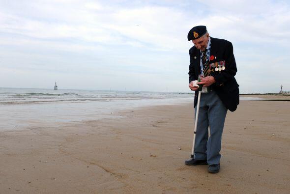 Un veterano de la Segunda Guerra Mundial recoge una concha mientras da u...