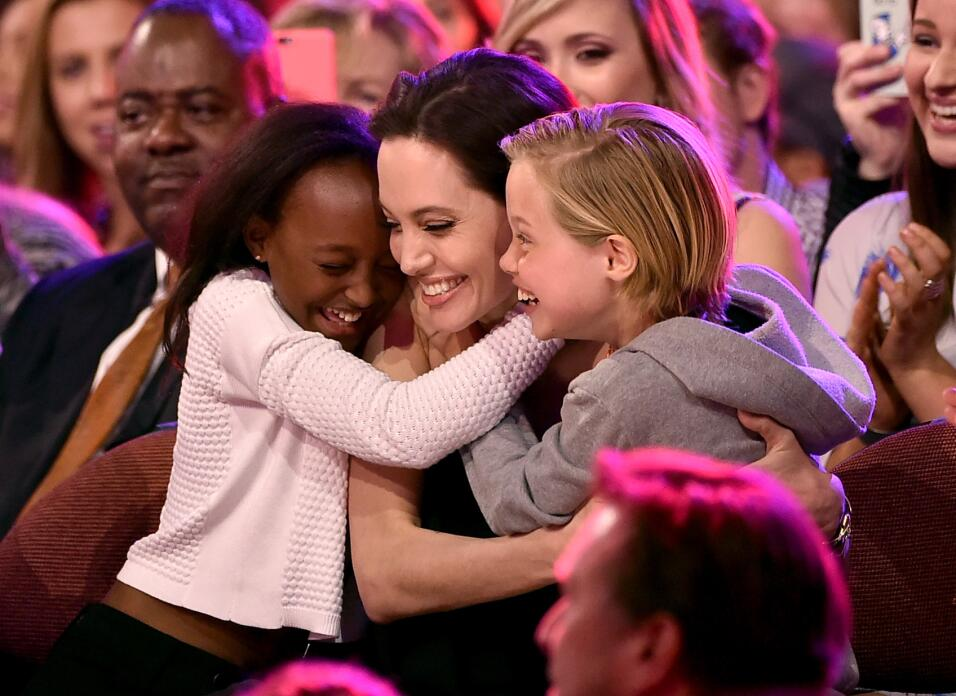 Actress Angelina Jolie hugs Zahara Marley Jolie-Pitt (L) and Shiloh Nouv...