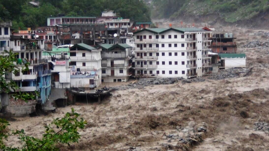Fast moving water from the  Alaknanda river destroys building during a h...