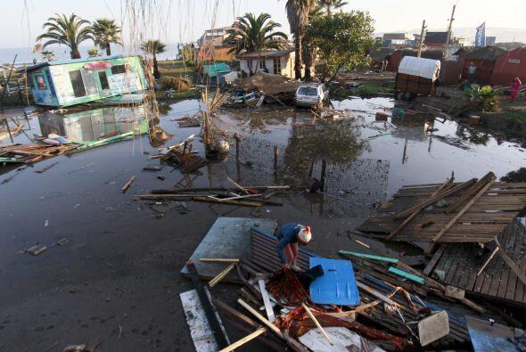 Una mujer camina entre los destrozos causados por las aguas tras el terr...