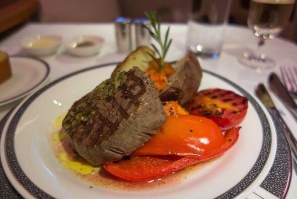 Un pedazo de filet mignon con verduras a la parrilla.