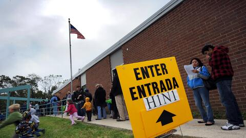 Personas esperan fuera de un centro de vacunación contra la influenza en...
