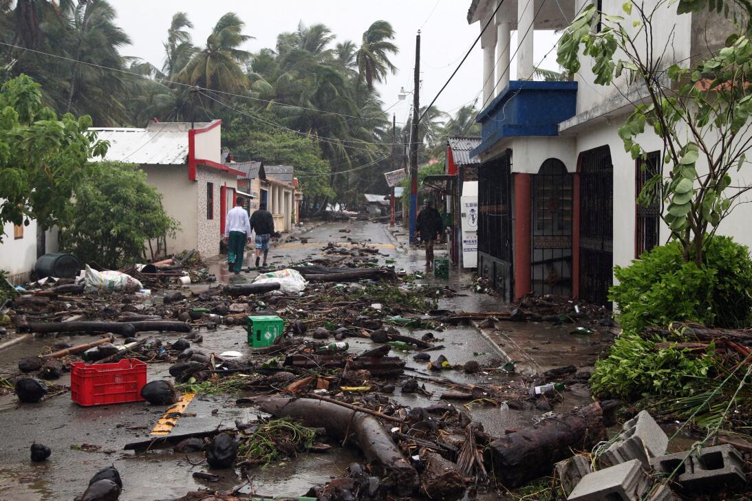 Tres personas caminan por una calle cubierta de escombros en la ciudad d...