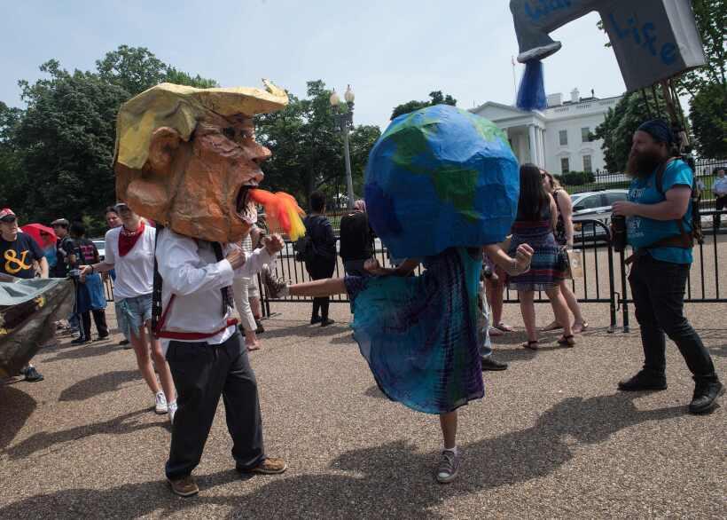 Manifestantes en máscaras del presidente Trump y la Tierra simulan pelea...