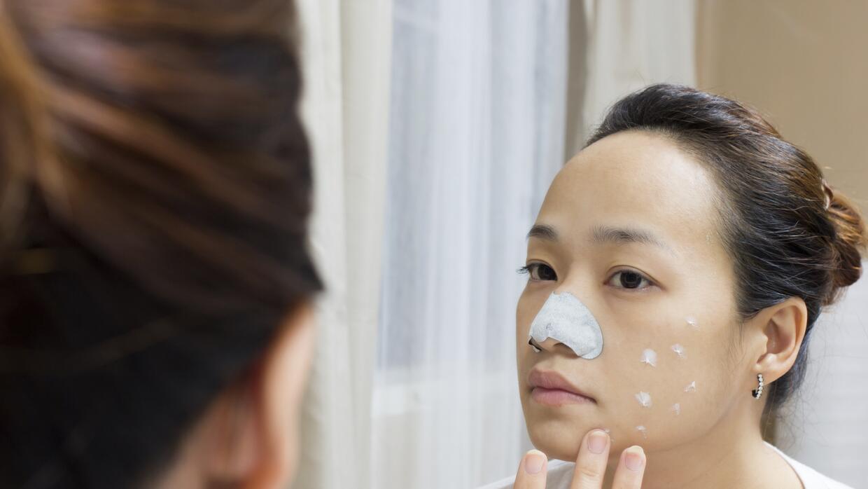 Mujer asiática untando crema en su rostro