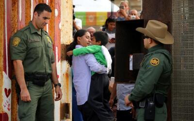 Dos agentes de la Patrulla Fronteriza resguardan a un migrante abrazando...