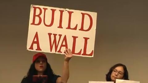 Una mujer sostiene un cartel pidiendo al construcción del muro fronteriz...