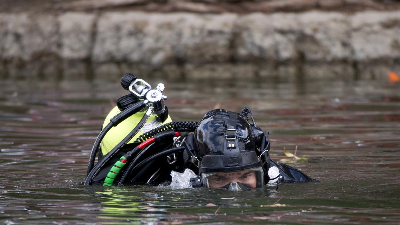 Un miembro del equipo de buceadores del FBI rastrea el lago Seccombe, el...