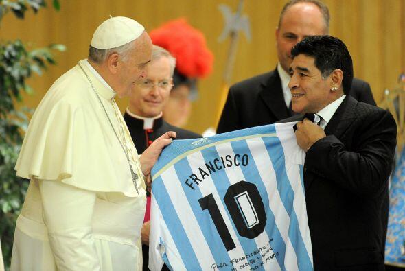 El papa Francisco recibe de manos del exfutbolista argentino Diego Arman...