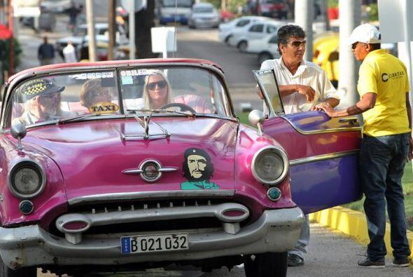 Un grupo de turistas espera en un vehículo clásico.