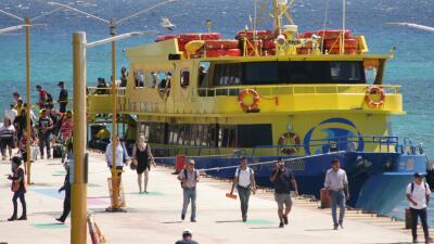 Turistas descienden de un ferry en Playa del Carmen, México.