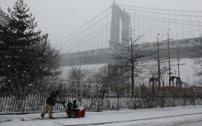 Un hombre limpia la veredea cerca del Puente de Brooklyn en Nueva York.